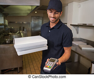 Happy pizza delivery man holding credit card machine in a...