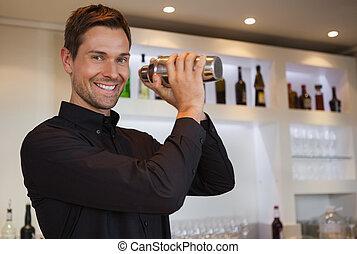 Smiling bartender shaking cocktail at the bar