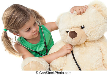 Cute little girl playing doctor with her teddy bear on white...