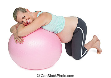 Cheerful pregnant woman kneeling against pink exercise ball...