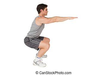 Fit man doing squats on white background