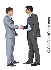 Happy business partners shaking hands on white background
