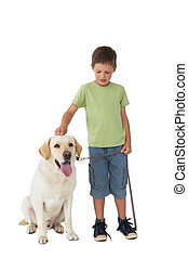 Cute little boy standing with his labrador dog on white...