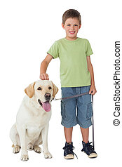 Cute little boy standing with his labrador dog smiling at...