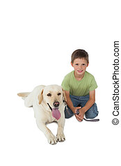 Cute little boy kneeling with his labrador dog smiling at...