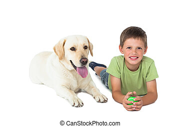 Cute little boy holding ball lying on floor with his...