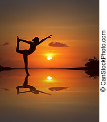 Silhouette of a beautiful Yoga woman in mirrored sunset beach