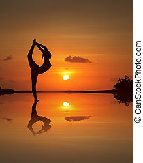 Silhouette of a beautiful Yoga girl on mirrored sunset beach