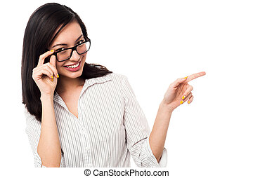 Woman adjusting her spectacles and pointing away - Young...