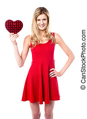 Pretty young girl holding heart shaped gift