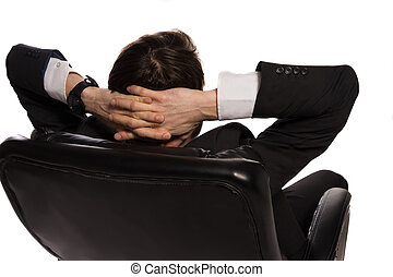 Relaxed businessman sitting in a comfortable chair - Rear...