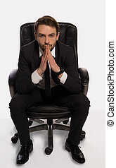 Businessman with a dilemma sitting in his office chair...