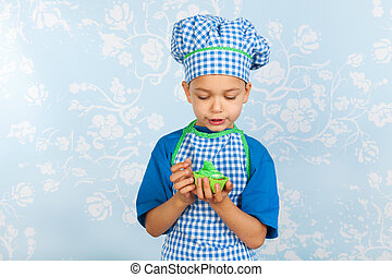 Little boy in apron baking cupcakes
