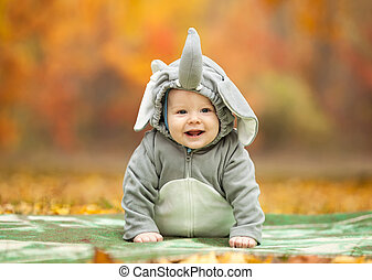 Baby boy dressed in elephant costume in autumn