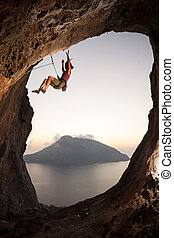 Climber falling of a cliff while lead climbing - Female rock...