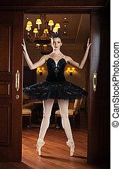 Ballerina in black tutu standing on pointes in doorway