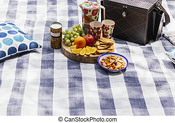 picnic setting with fresh fruit, snacks, blanket, pillow and...