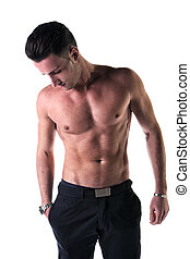 Handsome, fit young man shirtless with black pants, isolated...