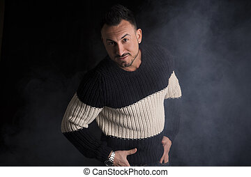 Good looking man standing, wearing winter sweater