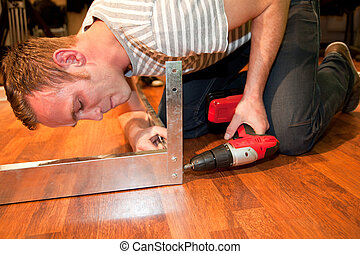 Young man doing DIY home improvements bending down on a...