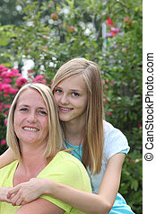Affectionate teenage girl posing with her mother hugging her...