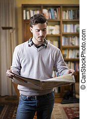 Handsome young man reading newspaper at home in his...