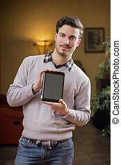 Handsome young man at home with tablet PC in his hands