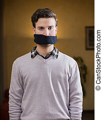Gagged young man cannot speak - Young man with gag (scarf)...