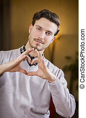 Handsome young man making heart sign with hands