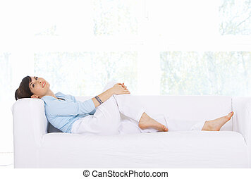 Daily life - Young woman relaxing on couch in her home