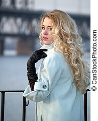Lady on promenade - Beautiful blonde lady in overcoat on...