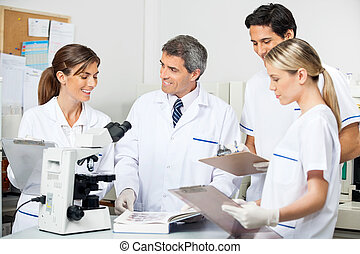 Researcher With Students Taking Notes In Lab - Mature male...