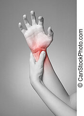 Wrist pain - A young woman massaging her painful wrist
