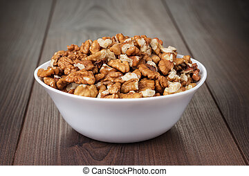 walnuts in the white bowl on wooden table - walnuts in the...