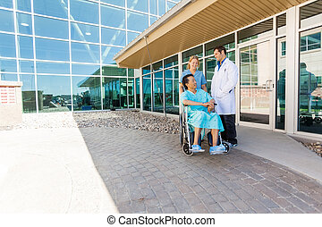 Nurse And Doctor Looking At Patient On Wheelchair At...
