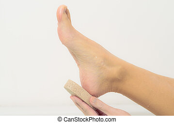 Woman using a pumice stone to exfoliate her feet - Woman...