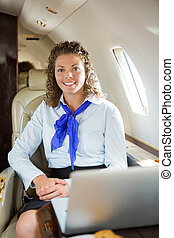 Happy Airhostess With Laptop In Private Jet - Portrait of...