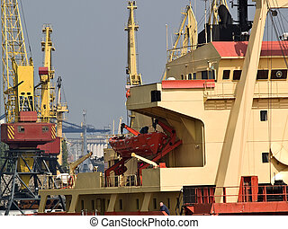 Ship in Port - A big vessel in port with cranes on...