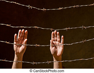 hand behind barbed wire with dark background
