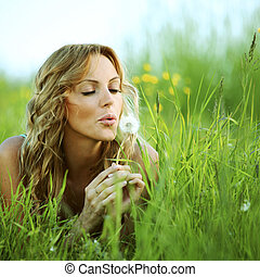 I wish - Young woman makes a wish blowing on dandelion