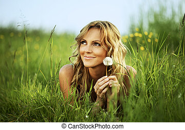 I wish - Young woman with dandelion lying on grass