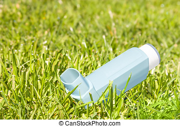 Asthma inhaler sprayer in blades of green grass - Open,...