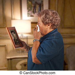 Remembrance - Old lady crying watching a photo of a deceased...