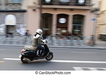 Woman on scooter with motion blur. Europe
