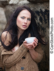 woman drinking tea outdoors - Young cute girl in a knitted...