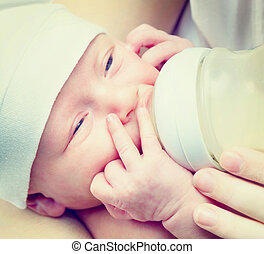 Feeding Baby. Newborn Baby eating milk from the bottle