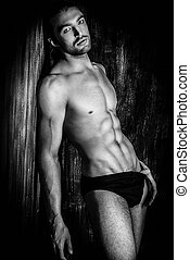 brawny - Sexual muscular nude man posing over dark...