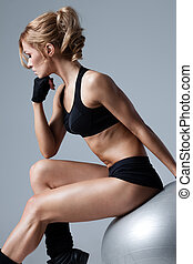 Fitness with gym ball - Athletic woman sitting on a gym ball...