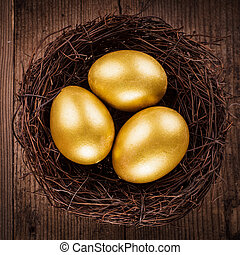 golden eggs in the nest over wooden background with copy...