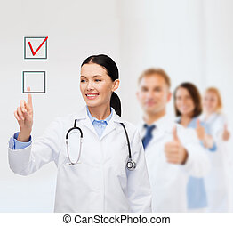smiling female doctor pointing checkbox - healthcare,...
